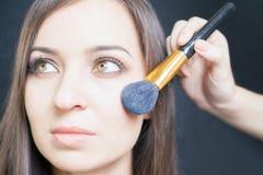 Makeupkonstnär som gör sminket för härlig caucasian kvinna Royaltyfri Fotografi