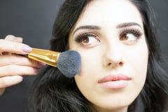 Makeupkonstnär som gör sminket för nätt arabisk kvinna Fotografering för Bildbyråer