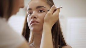 Makeupkonstnären applicerar ögonskugga, perfekt aftonmakeup Skönhetrödhårig manflicka med perfekta hud och fräknar lager videofilmer