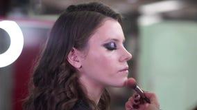 Makeupkonstnären applicerar makeup till attraktivt barn modellerar för fotoperiod arkivfilmer