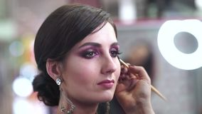 Makeupkonstnären applicerar makeup till attraktivt barn modellerar för fotoperiod lager videofilmer