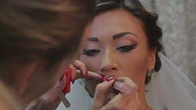 Makeupkonstnären applicerar makeup till en attraktiv brud arkivfilmer