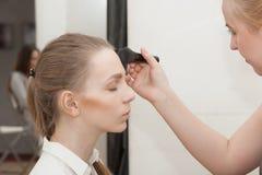 Makeupkonstnären applicerar makeupunga flickan för photoshooten Royaltyfri Bild