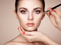 Makeupkonstnären applicerar skintone Arkivfoto