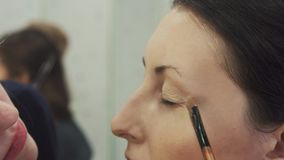Makeupkonstnären applicerar upp slut för ögonskugga arkivfilmer