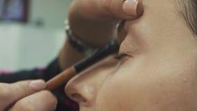 Makeupkonstnären applicerar upp slut för ögonskugga, makroen arkivfilmer