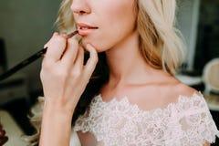Makeupkonstnären gör den unga härliga bruden brud- makeup Morgonförberedelse Närbilden räcker nära framsida arkivbilder