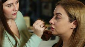 Makeupkonstnären gör en flicka härlig makeup arkivfilmer