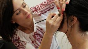 Makeupkonstnären gör makeup av en härlig brunettflicka stylist som arbetar på bilden av modellen makeupkonstnären drar ögon med stock video