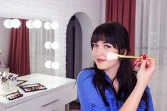 Makeupkonstnären gör makeup på framsida med makeupborsten arkivbild