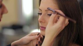 Makeupkonstnären gör perfekt makeup för ung flicka arkivfilmer