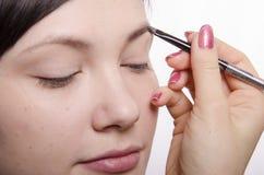 Makeupkonstnären i processen av makeup kommer med modellen för ögonbrynblyertspennan Royaltyfri Bild