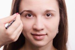 Makeupkonstnären kommer med borsteögonbrynflickan royaltyfria foton