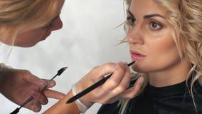 Makeupkonstnären målar kanterna av en ung kvinna i en skönhetsalong lager videofilmer