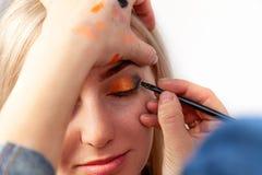 Makeupkonstnären med en borste i händerna med en plan kant målar pilen på ögonlocket av modellen, applicerar smink till ögonen royaltyfri foto