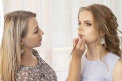 Makeupkonstnären sätter utgör på flickamodell bröllopmakeup, aftonmakeup, naturlig makeup sminkkonstnären målar kanter arkivfoton
