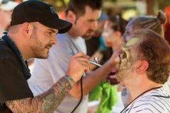 Makeupkonstnärer ger deltagare levande dödMakeovers för den Atlanta händelsen royaltyfria foton