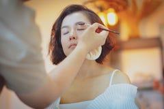 Makeupkonstn?r som arbetar p? h?rlig asiatisk modell arkivfoto