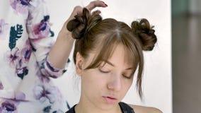 Makeupkonstn?ren g?r makeup av en h?rlig ung caucasian brunett lager videofilmer