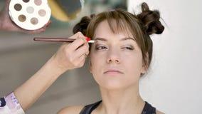 Makeupkonstn?ren g?r makeup av en h?rlig ung caucasian brunett arkivfilmer
