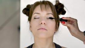 Makeupkonstn?ren g?r makeup av en h?rlig ung caucasian brunett stock video