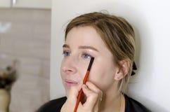 Makeupkonstn?ren g?r makeup f?r flickan fotografering för bildbyråer
