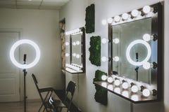 Makeupkonstn?rs arbetsplats en spegel med lampor p? en vit v?gg och en tr?f?t?lj arkivbild