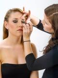 Makeupkonstnär som applicerar makeup på modell Arkivfoto
