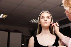 Makeupkvinna som baddar fundamentet på en klient Arkivfoton