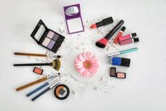 Makeupobjekt och blomma på vit bakgrund arkivfoton