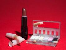 Makeupobjekt på röd bakgrund med hög-kontrast belysning Royaltyfri Bild