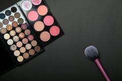 Makeuppalets och borste på ren svart bakgrund Arkivfoto