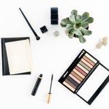 Makeuptabell Ögonskugga, mascara, suckulenter och anteckningsbok på whi Arkivfoton