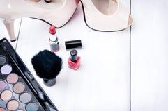 Makeuptillbehör, häl på en träträbakgrund royaltyfria foton