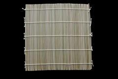 Maki de bambú de la estera para el sushi aislado en fondo negro imagen de archivo