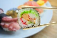Maki del sushi en palillos Imagen de archivo