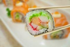 Maki del sushi en palillos Imágenes de archivo libres de regalías