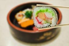 Maki del sushi en palillos Fotos de archivo