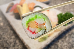 Maki del sushi en palillos con el sistema del sushi Fotos de archivo