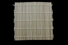 Maki di bambù della stuoia per i sushi isolati su fondo nero immagine stock