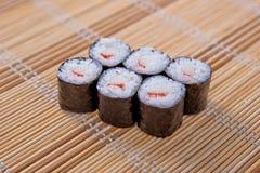 Maki (petit pain de sushi) sur un placemat en bambou Images stock