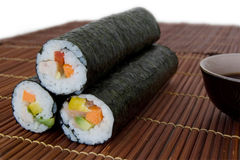Maki Rolls. Three nori rolls on a bamboo mat and a bowl of soy sauce Royalty Free Stock Photo