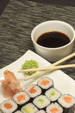 Maki rolls sushi on a plate. Maki rolls sushi and ginger with wasabi on a plate. In the background is a bowl with soy sauce and chopsticks. Vertically royalty free stock images