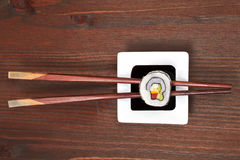 Maki sushi. Maki sushi on chopsticks on soy sauce in white bowl on dark wooden background stock images