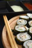 Maki sushi. Close-up of maki sushi rolls arranged on a plate with chopsticks, shallow dof, dips blurred in background Stock Photos