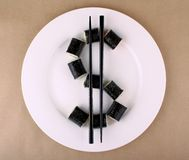 Maki Sushi as dollar sign on white plate Royalty Free Stock Images