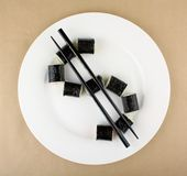Maki Sushi as dollar sign on white plate, close up Stock Photo
