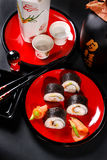 Maki sushi on red plate and sake Royalty Free Stock Image