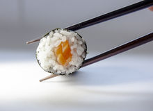 Maki (Sushi Roll) on chopstick. Japanese sushi roll on a chopstick Royalty Free Stock Images