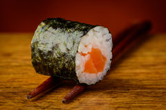 Maki sushi roll on chopsticks Stock Images